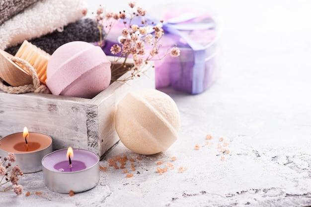 Kule do kąpieli o zapachu różowej wanilii w aranżacji spa z suszonymi kwiatami i zapaloną świecą