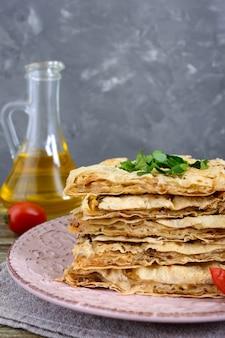 Kulebiak, zapiekanka pita z grzybami, twarożek i ser na talerzu na drewnianym tle. ciasto warstwowe. widok pionowy