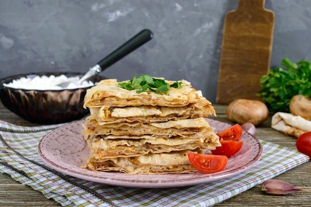 Kulebiak, zapiekanka pita z grzybami, twarożek i ser na talerzu na drewnianym tle. ciasto warstwowe.