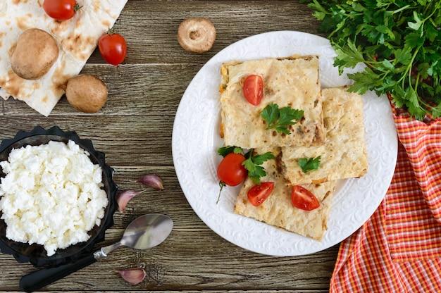Kulebiak, zapiekanka pita z pieczarkami, twarożek i ser na białym talerzu na drewnianym tle. ciasto warstwowe. widok z góry