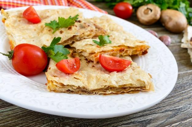 Kulebiak, zapiekanka pita z pieczarkami, twarożek i ser na białym talerzu na drewnianym tle. ciasto warstwowe.