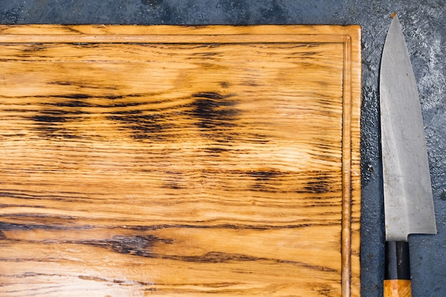 Kulinarna klasa mistrzowska. pusta drewniana deska do krojenia i nóż.