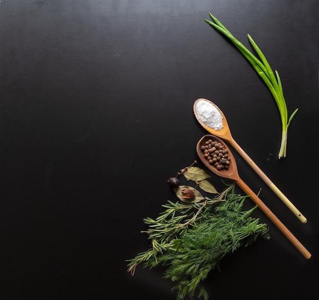Kulinarna martwa natura ze świeżymi aromatycznymi ziołami, liśćmi laurowymi, ziarnami pieprzu i drewnianymi łyżkami