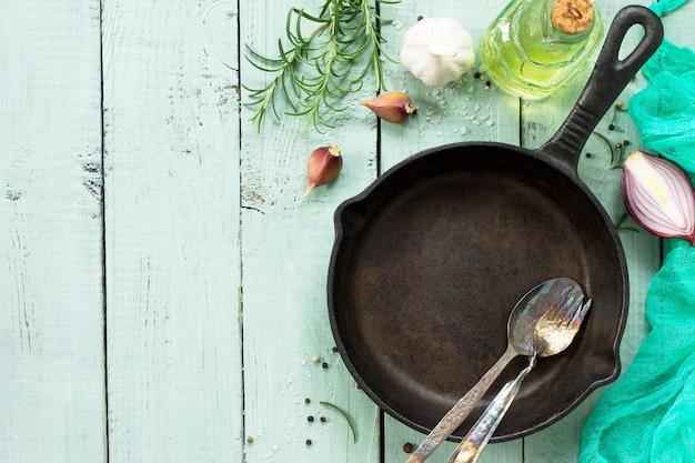 Kulinarna powierzchnia patelnia castiron świeży rozmaryn, czosnek oliwa z oliwek i przyprawy