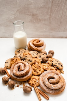 Kulinarne tło organiczne śniadanie ciasta, bliska wolna przestrzeń. pełnoziarniste bułeczki i pieczone bułeczki z orzechami włoskimi i cynamonem leżące w pobliżu butelki mleka. koncepcja sklepu domowego wypieków