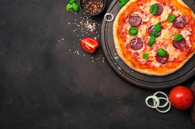 Kulinarne tło z pizzą pepperoni na brązowym tle z pomidorami i cebulą.
