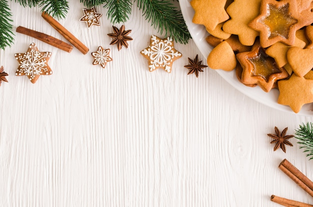 Kulinarne tło ze świeżo upieczonym świątecznym piernikiem, przyprawami i gałęziami jodły.