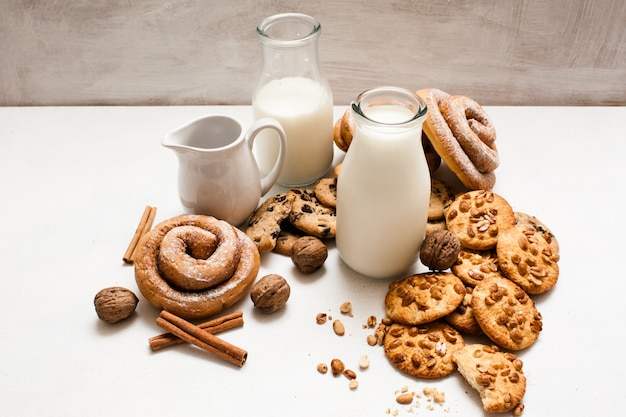 Kulinarne zaplecze domowego wypieku. pełnoziarniste bułeczki, pieczone bułki, orzechy włoskie i przyprawy leżące w pobliżu butelek mleka na białym stole. koncepcja pysznego rustykalnego śniadania z ciasteczkami