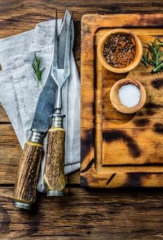 Kulinarny tła pojęcie. vintage deska do krojenia ze sztućcami. widok z góry
