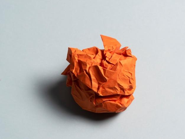 Kulka zmiętego papieru pomarańczowego na jasnym tle.