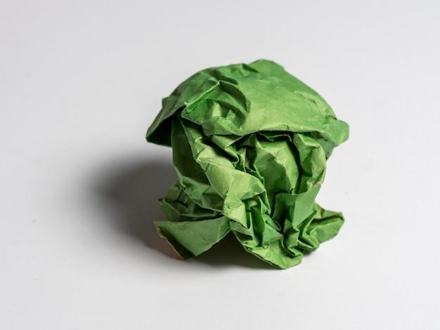 Kulka zmiętego zielonego papieru na jasnym tle.