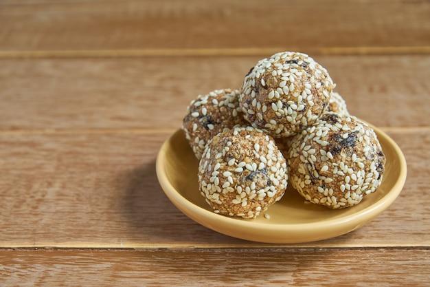 Kulki białka sezamowego z płatków owsianych. ukąszenia o niskiej zawartości tłuszczu z płatkami owsianymi, sezamem orzechowym i suszonymi śliwkami na drewnie