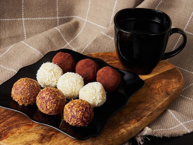 Kulki cukierki ręcznie robione na czarnym talerzu i czarnej filiżance