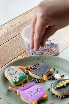 Kulki cukru w słoiku. na niewyraźnym pierwszym planie cukiernik dekorujący maślane ciasteczka.