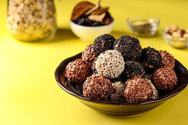 Kulki energetyczne i składniki: orzechy, płatki owsiane i suszone owoce na talerzu na żółtej powierzchni, ułożenie poziome, zbliżenie
