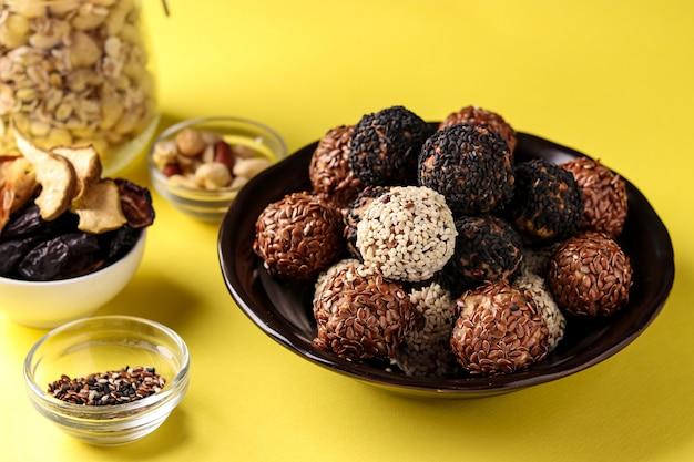Kulki energetyczne i składniki: orzechy, płatki owsiane i suszone owoce na talerzu na żółto,
