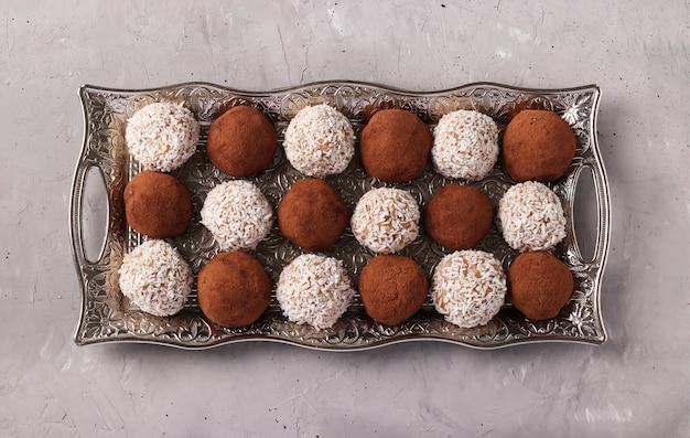 Kulki energetyczne orzechów i płatków owsianych z kokosem i kakao na metalowej tacy na szarej betonowej powierzchni, format poziomy, widok z góry