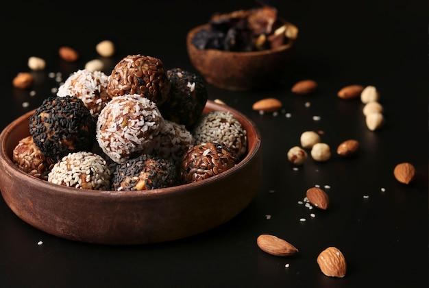 Kulki energetyczne orzechów, płatków owsianych i suszonych owoców na brązowym talerzu na czarnym tle, format poziomy, zbliżenie