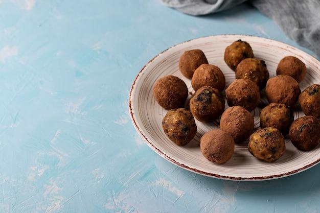 Kulki energetyczne z ciecierzycy, suszonych śliwek i daktyli posypane kakao na talerzu na jasnoniebieskiej powierzchni, orientacja pozioma, widok z góry, miejsce na kopię