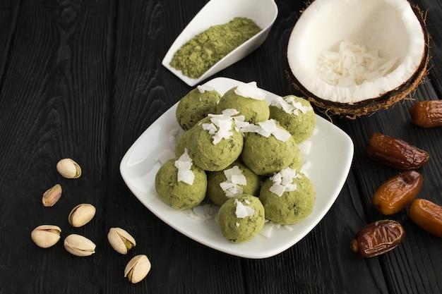 Kulki energetyczne z proszkiem matcha, pistacjami, daktylami i wiórkami kokosowymi na białym talerzu