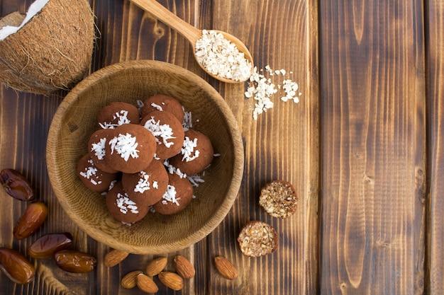 Kulki energetyczne z wiórkami kokosowymi, migdałami, płatkami owsianymi i daktylami w brązowej misce