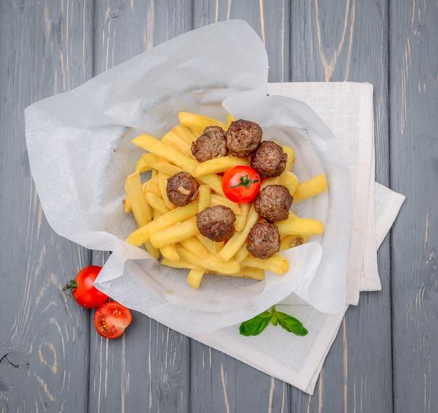 Kulki mięsne z grilla z frytkami na drewnianym