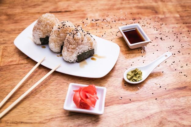 Kulki ryżowe onigiri na talerzu i sosie