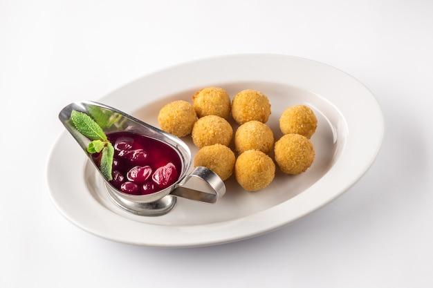 Kulki serowe głęboko smażone z sosem na białym talerzu