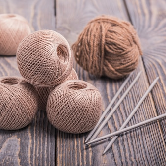 Kulki z przędzy i igły do robienia na drutach na drewnianej przestrzeni.