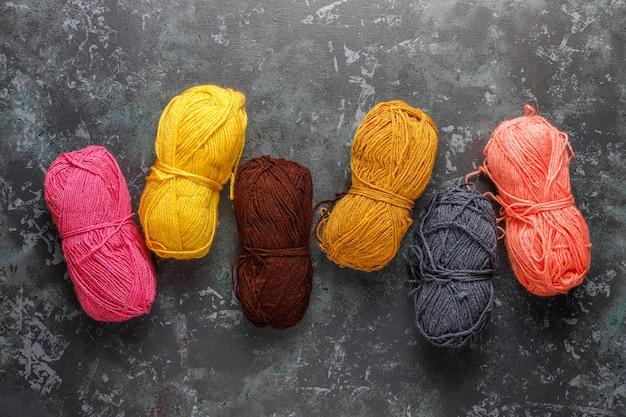 Kulki z przędzy w różnych kolorach z igłami do robienia na drutach.