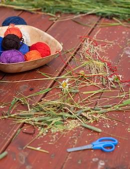 Kulki z wełnianej przędzy do dziania na drewnianym stole dzierganie w naturze robótki ręczne w ogrodzie