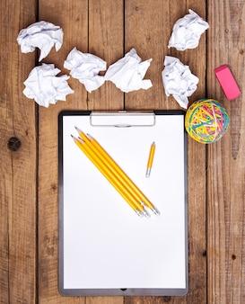 Kulki zmięty papier z ołówkiem i schowkiem na podłoże drewniane