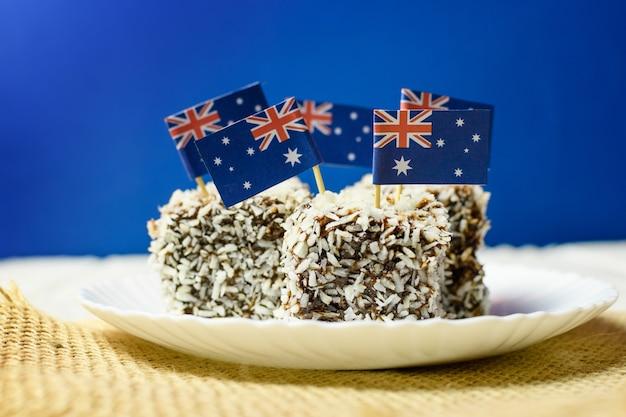 Kultowe tradycyjne australijskie przyjęcie, ciasta lamington na czerwonym, białym i niebieskim tle. flaga australii.