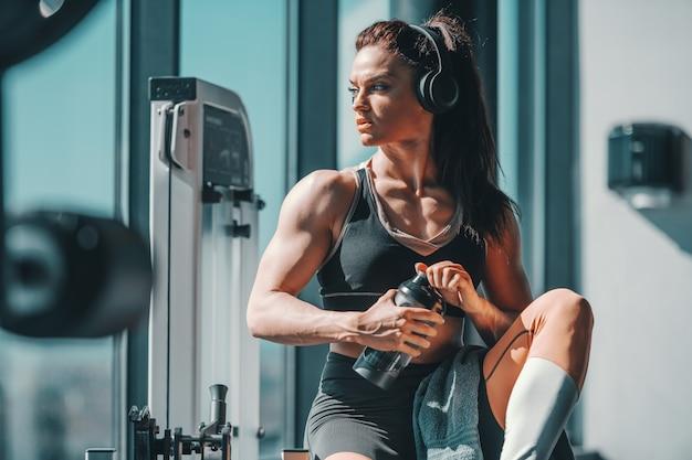 Kulturysta kobieta siedzi w siłowni ze słuchawkami na uszach i wody w rękach. nie ma znaczenia, jak wolno jedziesz, dopóki się nie zatrzymasz.