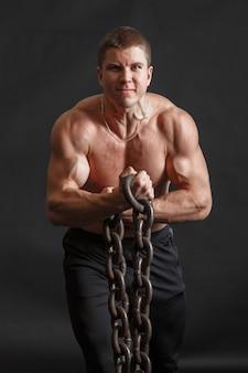 Kulturysta mężczyzna pozuje z żelaznym łańcuchem w jego rękach