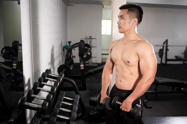 Kulturysta mięśni fitness mężczyzna jest trening z hantlami w siłowni