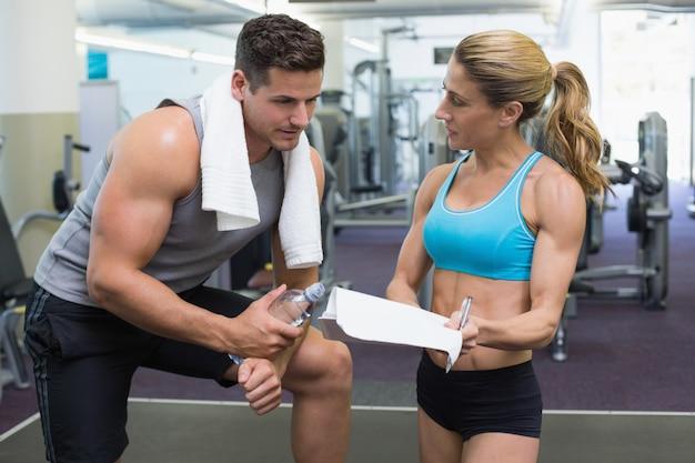 Kulturysta mówi ze swoim osobistym trenerem na siłowni