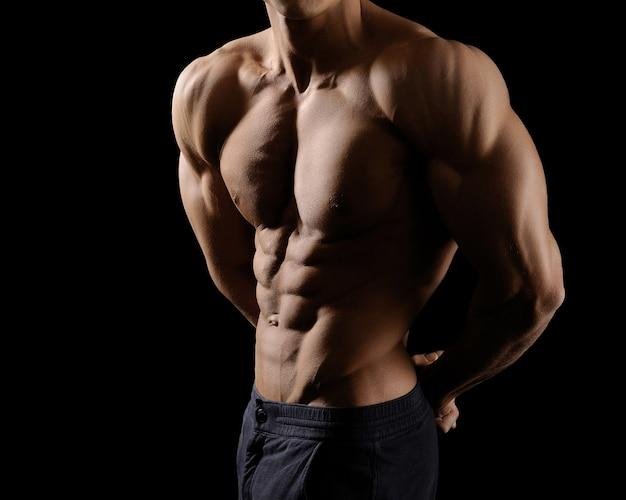 Kulturysta, pokazując swoje zgrane mięśnie brzucha pozuje bez koszuli w studio