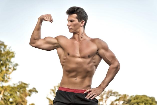 Kulturysta pokazujący mięśnie, bicepsy i triceps. fitness i sport. sportowiec z gołym torsem, sześciopak i ab. pojęcie zdrowego stylu życia. mężczyzna lub sportowiec wygina ramię na białym niebie.