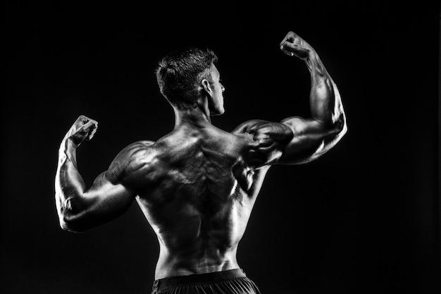 Kulturysta pozowanie. piękny sportowy facet męskiej mocy. fitness umięśniony mężczyzna