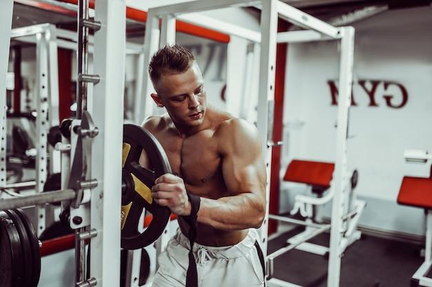 Kulturysta przygotowuje się do ćwiczeń ze sztangą w siłowni