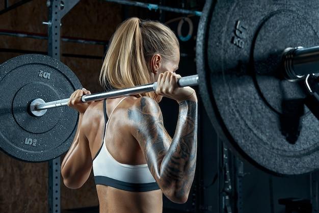 Kulturysta robi przysiady na siłownię piękna młoda brunetka gotowa do przysiadów ze sztangą