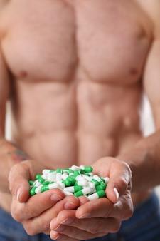 Kulturysta sportowiec przyjmuje leki w postaci tabletek w postaci szybkich postępów farmaceutycznych w rozwoju mięśni