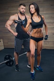 Kulturysta z brodą trenuje sportową dziewczynę w czarnym podkoszulku i szortach, która robi loki na bicepsie