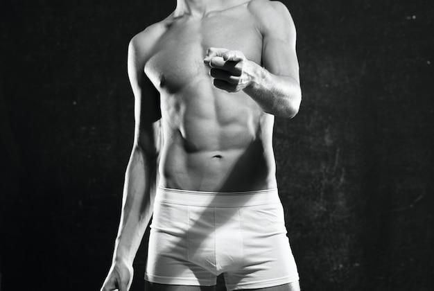 Kulturysta z napompowanym ciałem w białych majtkach pozuje na ciemnym tle