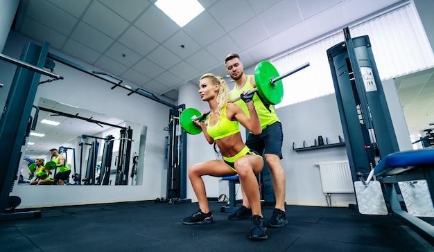 Kulturystyka. silna sprawna kobieta ćwiczenia z hantlami. mięśni blondynka podnoszenia ciężarów w siłowni.
