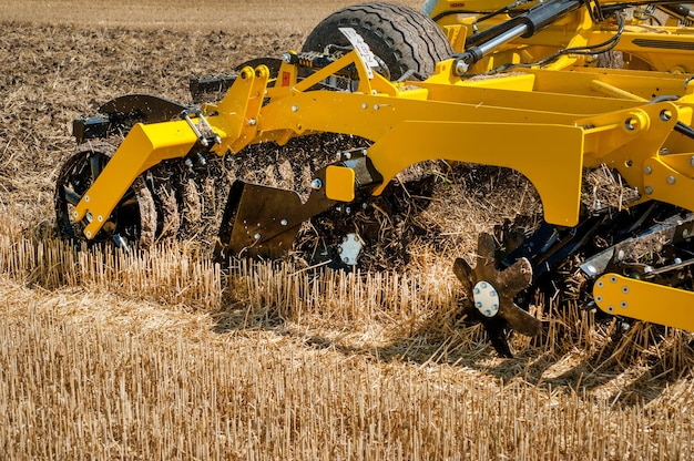 Kultywator w pracy, zbliżenie brony talerzowej na tle pola