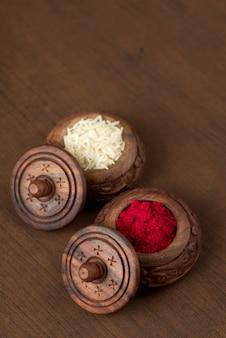 Kumkum i pojemnik na ziarno ryżu. proszki o naturalnym kolorze są używane podczas wielbienia boga i przy pomyślnych okazjach.