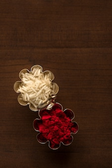 Kumkum i pojemnik ziarna ryżu na drewniane tła.