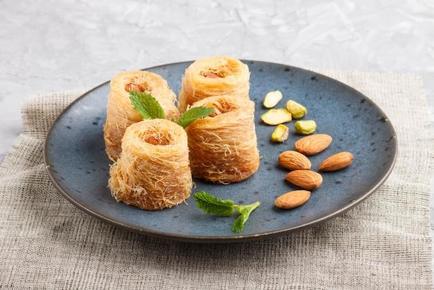Kunafa, tradycyjne arabskie słodycze w niebieskim talerzu ceramicznym
